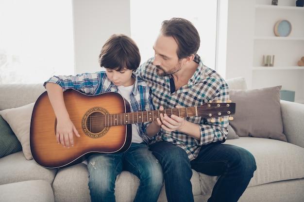 최고의 교사는 친척 개념입니다. 소파 룸 하우스에 앉아 격자 무늬 캐주얼 셔츠를 입고 악기 손을 잡고 기타를 연주하는 방법을 배우도록 학생을 돕는 집중된 성숙한 아버지