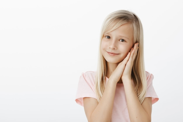 Best time spending is sleep. portrait of friendly-looking adorable female child with blond hair, smiling cheerfully and holding palms together near cheek, standing like angel over gray wall