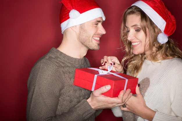 Best time of the year. studio portrait of a young loving christmas couple opening a present together laughing happily on red