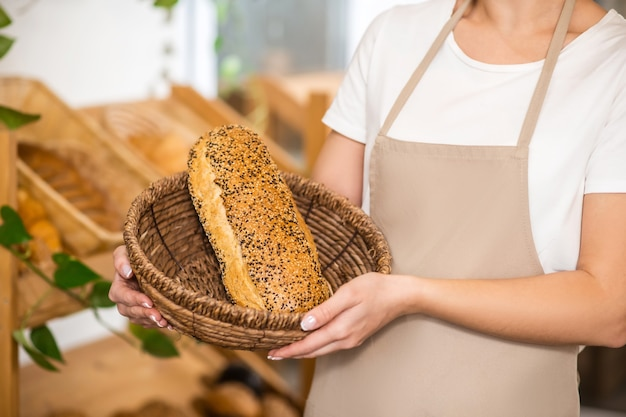 Best tradition. neat graceful female hands carefully holding basket with freshly baked beautiful loaf of bread