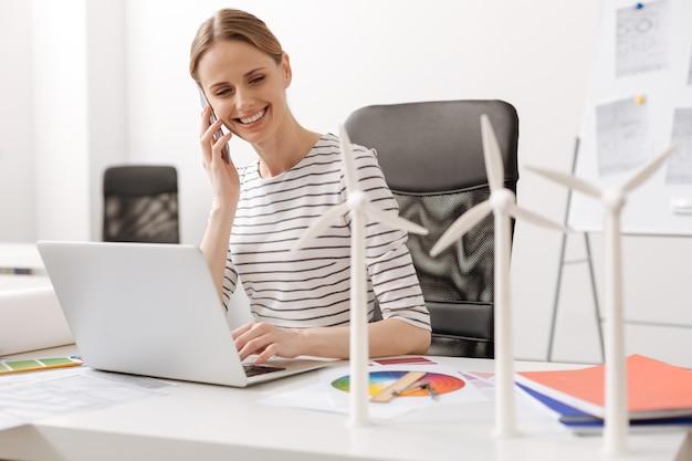 소통하는 가장 좋은 방법. 바람 터빈을 설계하는 동안 테이블에 앉아 스마트 폰으로 이야기하는 긍정적 인 매력적인 전문 여성