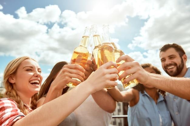 幸せな若者の最高の週末のグループは、ビールでボトルをチリンと鳴らしながら笑っています