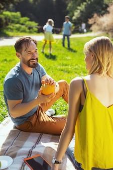 最高の週末。彼らの子供たちがバックグラウンドで遊んでいる間彼の妻と話しているハンサムな喜んでいる男