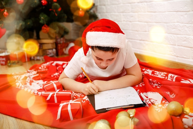 サンタの家に手紙を書いている友人の幸せな子供の男の子のための最高の願い