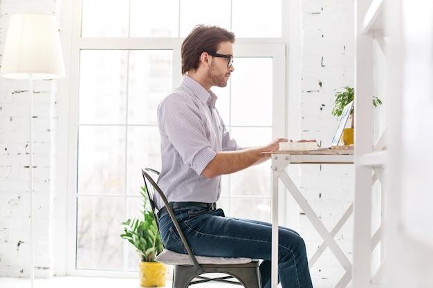 最高の労働者。テーブルに座って彼のラップトップで作業しているプロのひげを生やした男