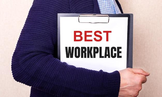Наилучшее рабочее место написано на белом листе, который держит человек, стоящий боком.
