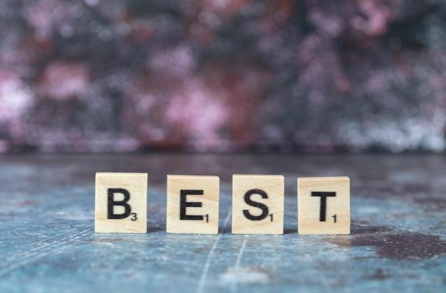 Migliore scrittura con lettere nere su dadi di legno su sfondo blu. foto di alta qualità