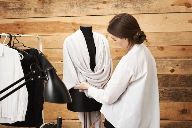 Bet it would look great on model. focused talented clothes designer trying her garment on mannequin, preparing for fashion week in her wooden tailor shop. creative sewer thinking about new concept