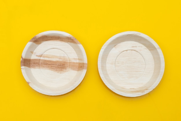 Betel palm leaf plates on yellow background.