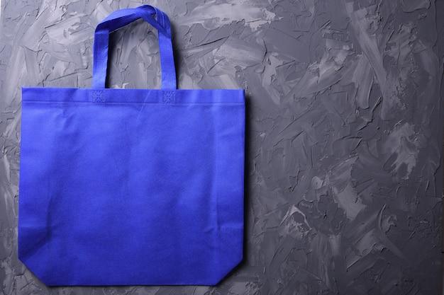 Betonの背景に青い繊維バッグ