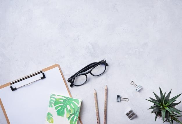 宿題。ビジネスフラット横たわっていたメモ、鉛筆、眼鏡、多肉植物、白いbetonの背景に