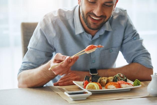 스시를 먹고 웃는 잘 생긴 사업가의 더 나은 음식 더 나은 분위기 자른 이미지