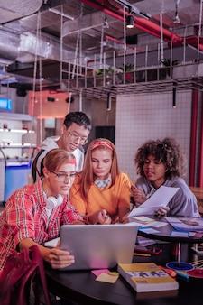 Лучше вместе. очаровательная девушка сидит между одноклассниками, глядя на компьютер