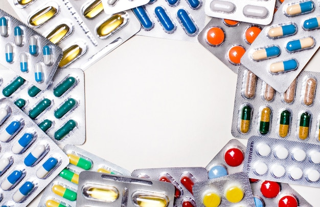 Между блистерами с разноцветными яркими таблетками остается пустое место для вставки текста. шаблон. медицинская концепция