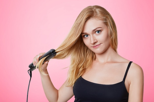 Beuatiful woman uses hair straightener for straightening hair, advertises its wonderful effect, isolated on pink. pretty female cares hair, makes hairdo. people and hairstyle concept