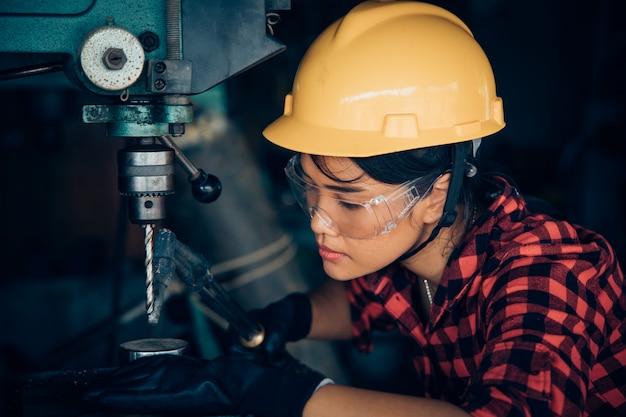 Азиатская beuatiful женщина, работающая с машиной в фабрике инженера и работницы концепции или женский день