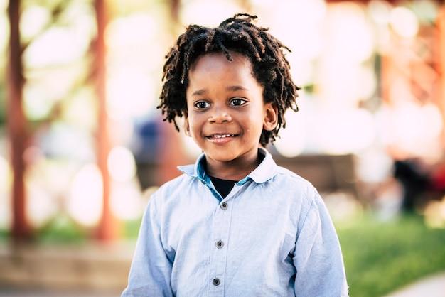 Красивый черный африканский народ, детский портрет с парком на открытом воздухе, расфокусированным цветом поверхности и разнообразием расы кожи, детская концепция с веселым ребенком, улыбающимся и счастливым, альтернативные волосы дреды