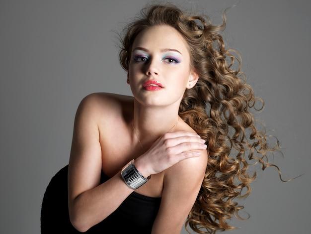 Красивый гламурный портрет молодой стильной женщины с длинными волосами, позирующей