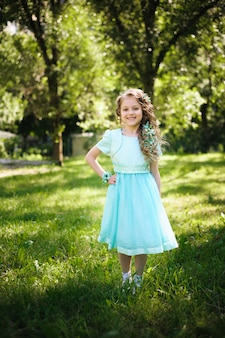 Beutiful little girl smiling looking at camera in the blooming spring garden