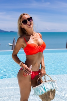 Beutiful tanned fit caucasian woman bronze shiny skin in bikini with coconut oil
