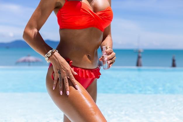 Beutiful tanned fit caucasian woman bronze shiny skin in bikini with coconut oil