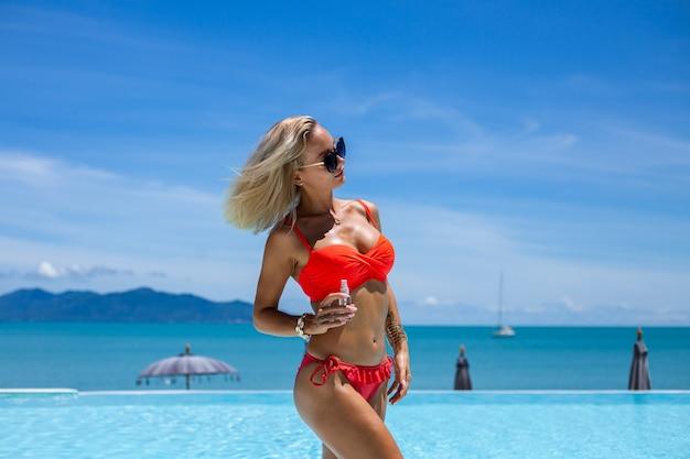 Красивая загорелая подтянутая кавказская женщина с бронзовой блестящей кожей в бикини с кокосовым маслом