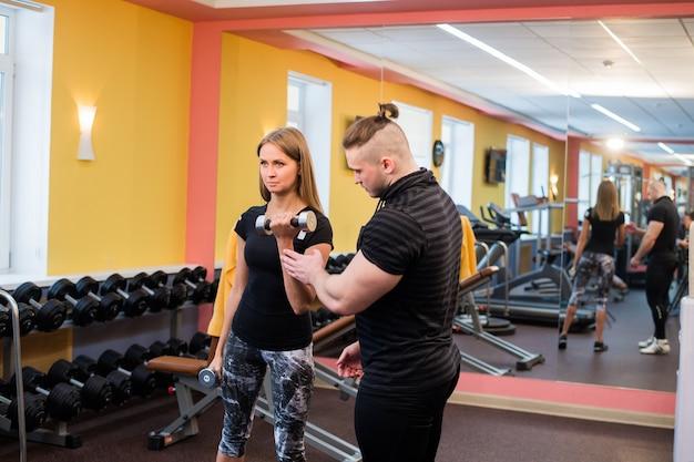 筋肉のトレーナーが彼女を支援しながらベンチに座ってダンベル運動をしている美しいヨン女性