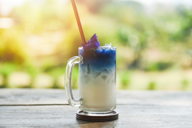 Beverage of butterfly pea drink glass on wooden table