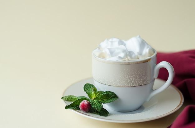 Напитки, напитки, кофе, капучино, какао, горячий шоколад со взбитыми сливками, клюква, мята на желтом фоне с копией пространства.