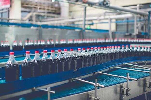 음료 공장 내부입니다. 탄산수 병이 흐르는 컨베이어.