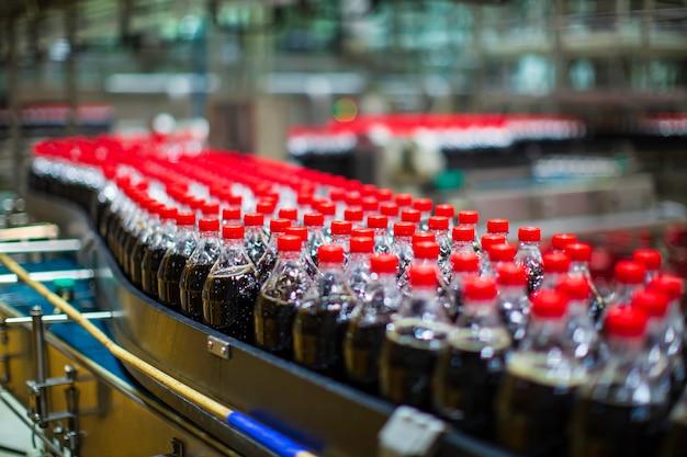飲料工場のインテリア。炭酸水用のボトルが流れるコンベヤー。