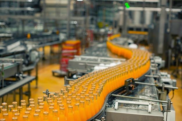 Интерьер завода по производству напитков. конвейер с бутылками для сока или воды.