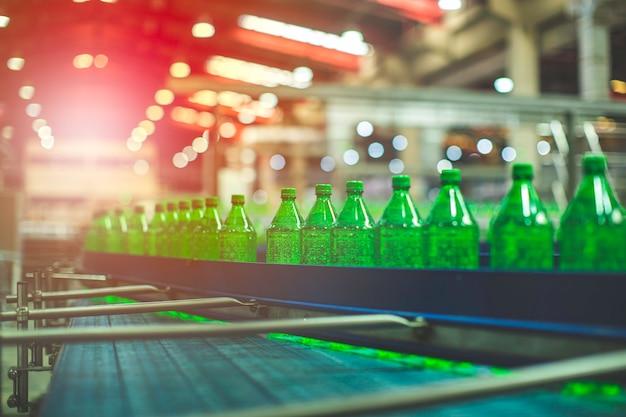 飲料工場のインテリア。水のために緑のボトルで流れるコンベヤー。