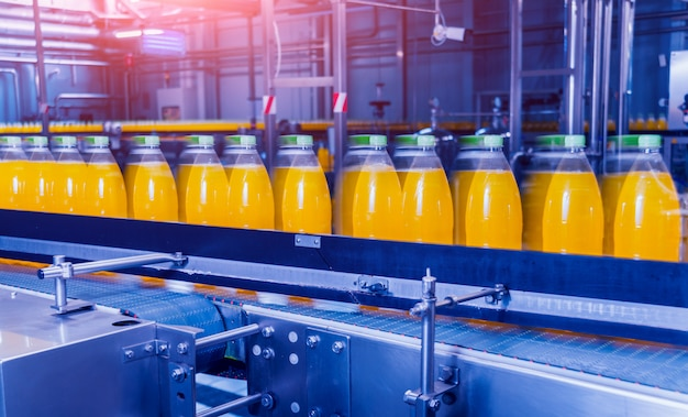 飲料工場のインテリア。ジュースまたは水のボトルが付いているコンベヤー。装備