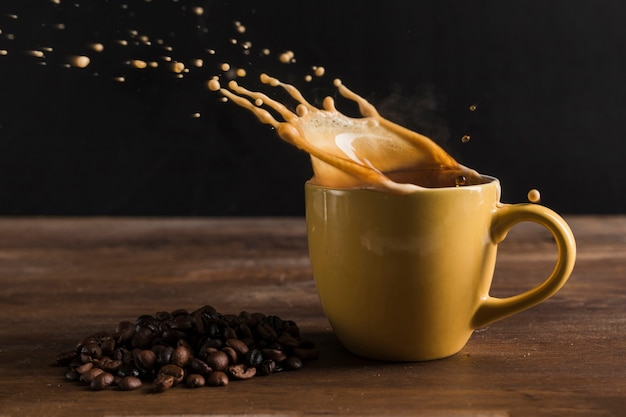 Beverage splashing out from cup near coffee beans