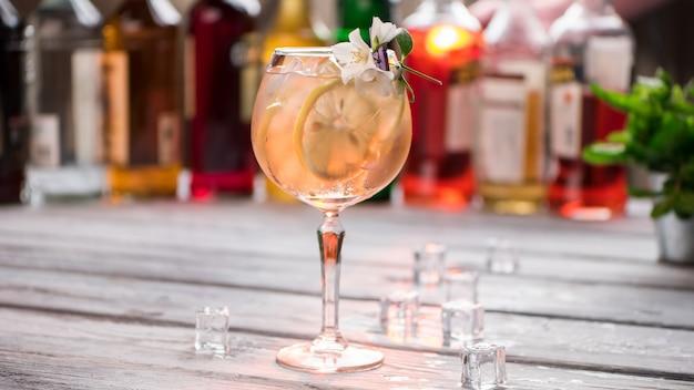 レモンのスライスと飲み物。ワイングラスの近くの氷の立方体。トム・コリンズの甘い味。涼しさはあなたをリラックスさせます。