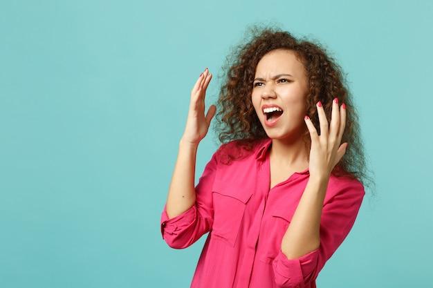 어리둥절한 아프리카 소녀는 평상복을 입고 욕설을 하고, 옆을 바라보며, 푸른 청록색 벽 배경에 격리된 손을 벌리고 있습니다. 사람들은 진심 어린 감정, 라이프 스타일 개념입니다. 복사 공간을 비웃습니다.