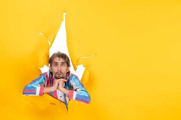 引き裂かれた黄色の紙の穴の背景に当惑し、感情的な若い男