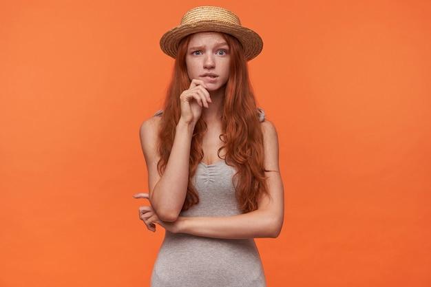 Sconcertata bella giovane femmina con capelli ondulati foxy in piedi su sfondo arancione in abiti casual camicia grigia cappello di paglia, tenendo la mano sul mento e guardando dubbioso alla fotocamera