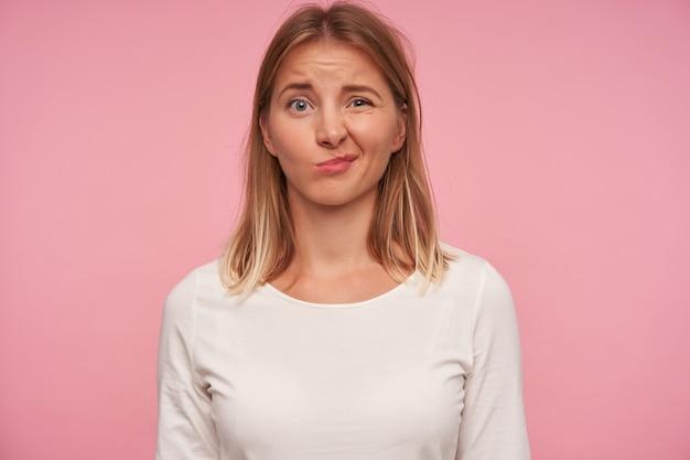 분홍색 배경 위에 포즈를 취하는 동안 캐주얼 한 옷을 입고 혼란스러운 얼굴로 카메라를보고 찡그린 금발 머리를 가진 당황한 파란 눈 예쁜 여성