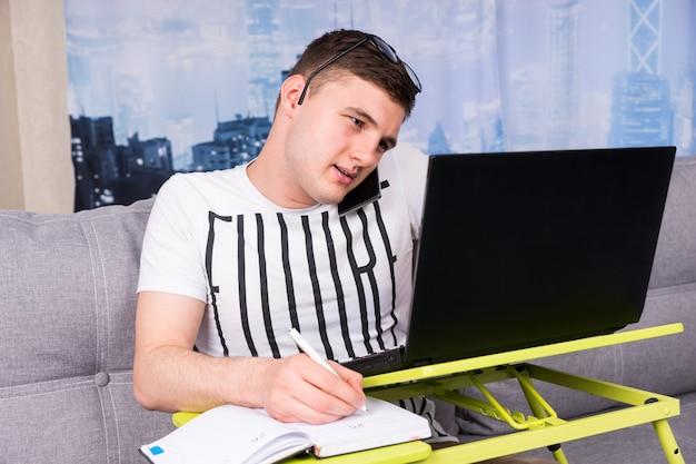 안경을 쓰고 집에서 노트북 작업을 하는 어리둥절한 잘생긴 청년이 집에서 펜을 들고 화면의 정보를 읽을 때