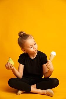 レオタードとダンスシューズを履いて、健康的な食べ物と不健康な食べ物のどちらかを選択し、黄色の背景に足を組んで座ってアイスクリームを見ている当惑した少女