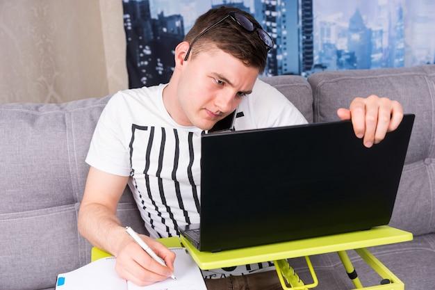 안경을 쓰고 집에서 노트북 작업을 하는 어리둥절한 남성이 화면의 정보를 읽을 때 펜을 들고 집에서 일을 하고 있다