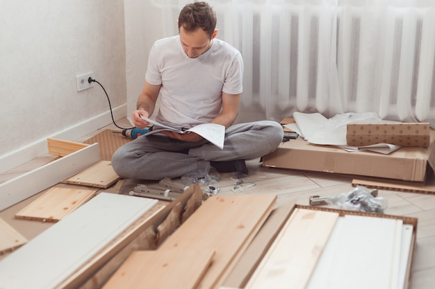 Bewildered man assembling wooden furniture