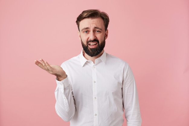 Bewildered pretty bearded brunette guy with trendy hairstyle raising palm with displeased face, frowning eyebrows with pout and raising hand while posing over pink wall