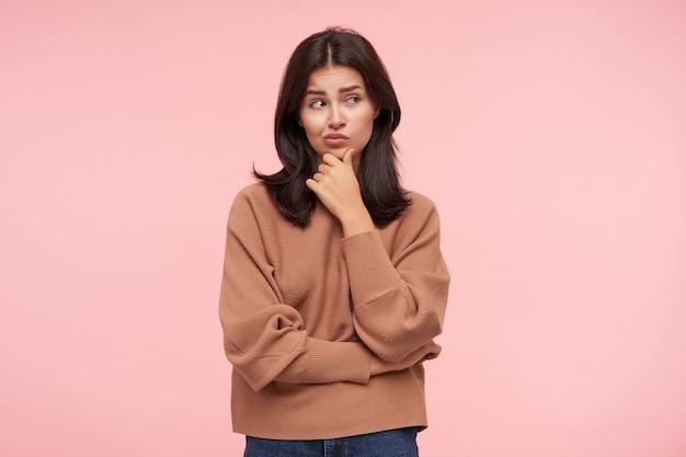Озадаченная молодая привлекательная шатенка, одетая в вязаный свитер с круглым вырезом, касается подбородка поднятой рукой и задумчиво смотрит в сторону, позируя над розовой стеной.