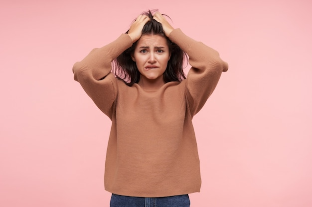 Bewildered young attractive brown haired woman keeping raised hands on her head and biting worringly her lips, standing over pink wall in casual clothes