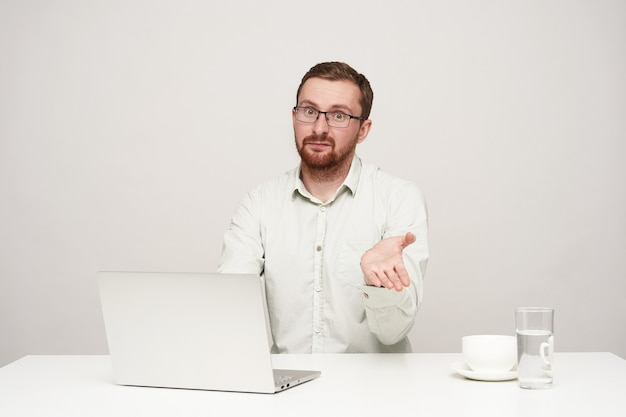 Bewildered young bearded fair-haired man with short haircut raising his hand while looking confusedly at camera, posing over white background in formal clothes