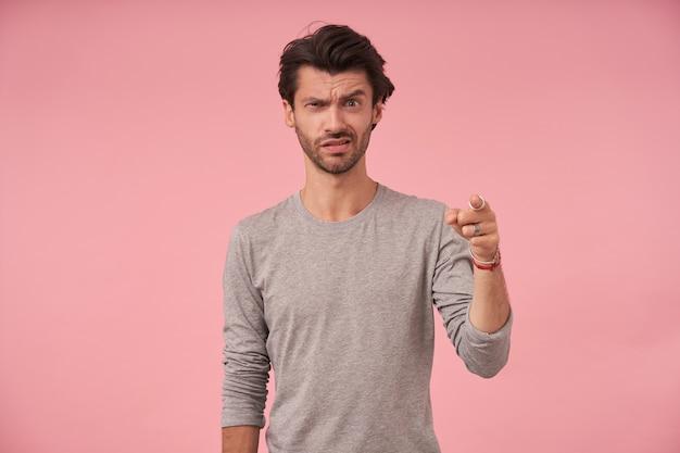 트렌디 한 헤어 스타일을보고 찡그린 얼굴을하고, 회색 스웨터에 서서, 인덱스 figer로 앞을 가리키는 당황한 젊은 수염 난 남성