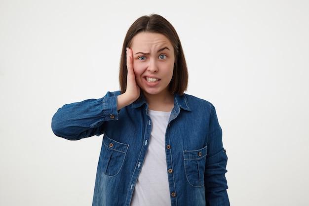 짧은 머리가 그녀의 뺨에 손바닥을 유지하고 흰 벽 위에 포즈를 취하는 동안 혼란스럽게 그녀의 얼굴을 찡그린 당황한 젊은 파란 눈 갈색 머리 아가씨